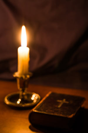 Candle Burning Next to Bible